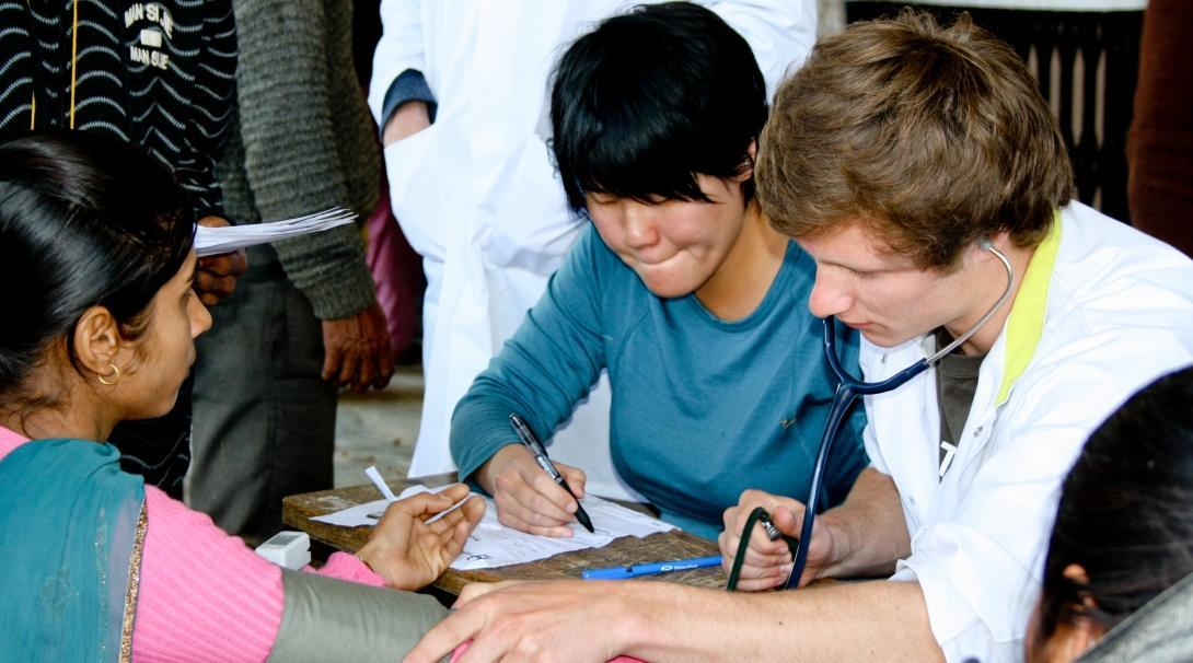A male intern can be seen performing a check up on a local patient during his nursing internship in Nepal with Projects Abroad.
